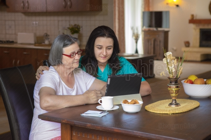 Caregiver with elderly woman using digital tablet at home