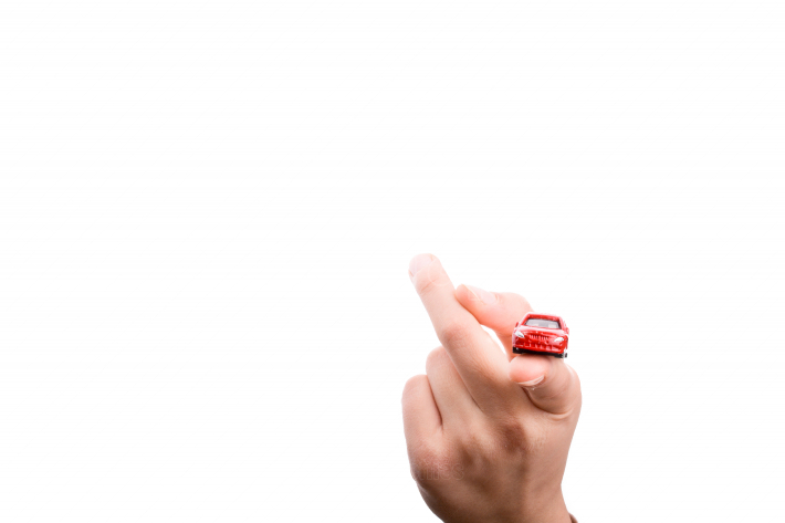 Child hand holding a red car