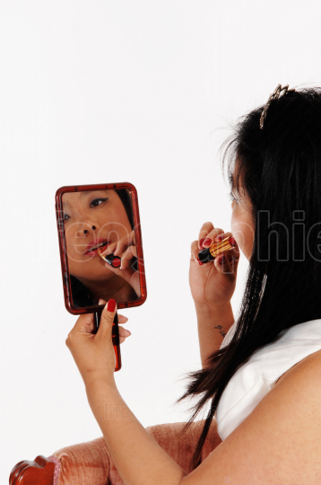 Chinese woman fixing her lipstick holding a mirror