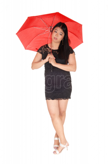 Chinese woman standing with a red umbrella legs crossed