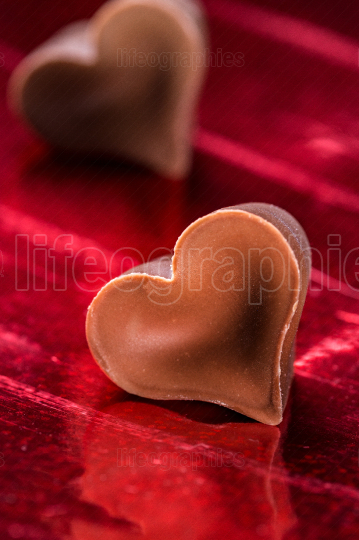 Chocolate hearts over red background