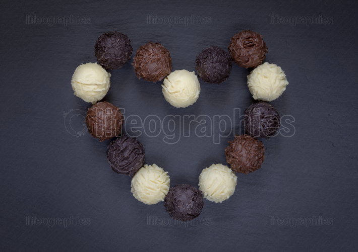 Chocolate truffles heart shape on black