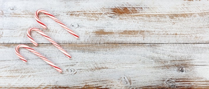 Christmas candy canes on white rustic wooden background
