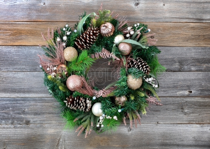 Christmas holiday wreath with illuminated lights on rustic wood