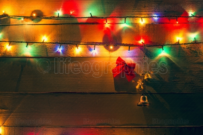 Christmas lights and bells on wood background