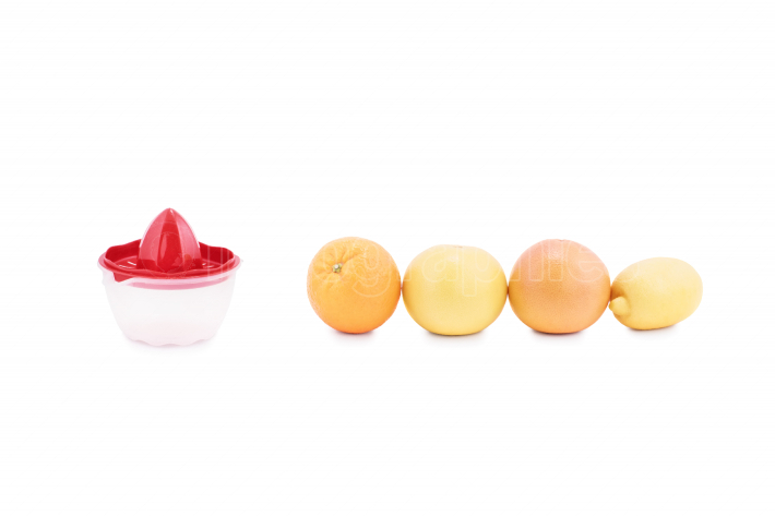 Citrus fruits arranged in a line next to a juice squeezer