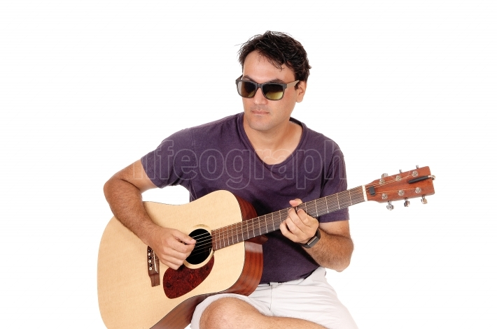 Close up image of man playing his guitar