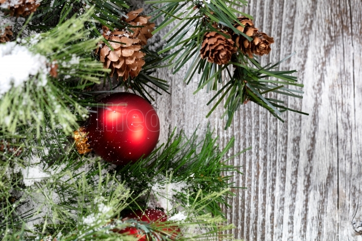 Close up of a red Christmas ball ornament on white rustic wood