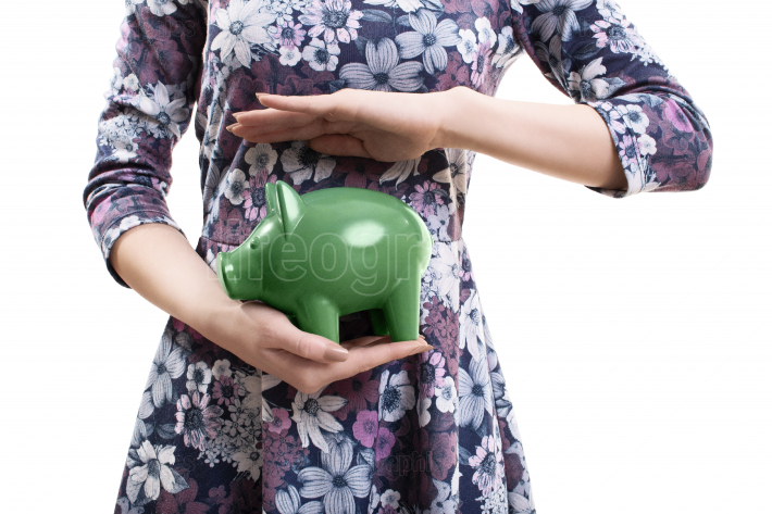 Close up of a young woman holding a piggy bank