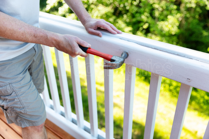 Close up of mature man hammering nail into white railing of outd