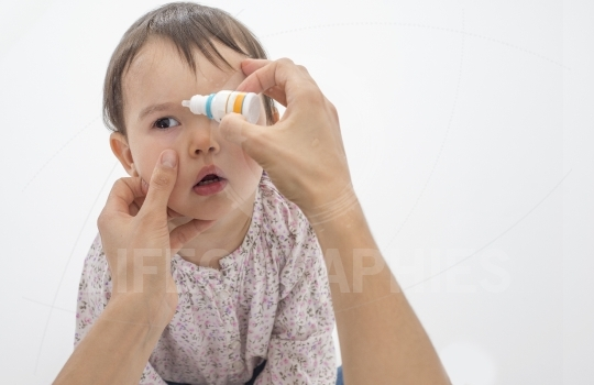 Closeup of mother pouring eye drops in the eye of her daughter