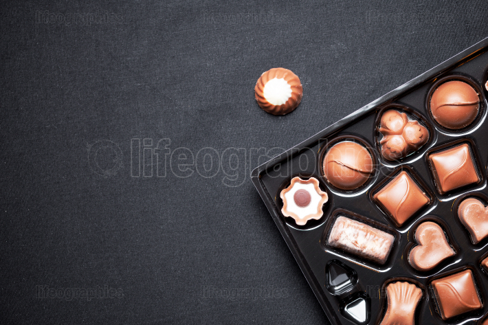 Closeup view of box of chocolates with variety chocolates pralines