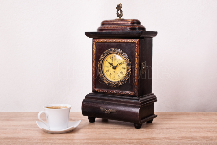 Coffee cup near an old fashioned antique clock