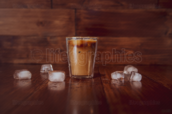 Coffee with milk and ice on wooden background