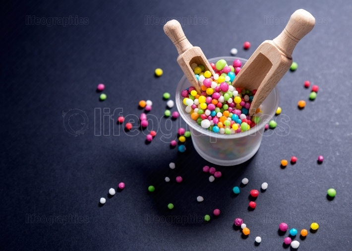 Colored candy,sugar pearls with wood scoop on black background