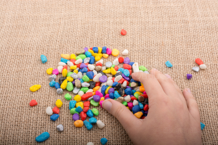 Colorful little pebbles in hand and on ground