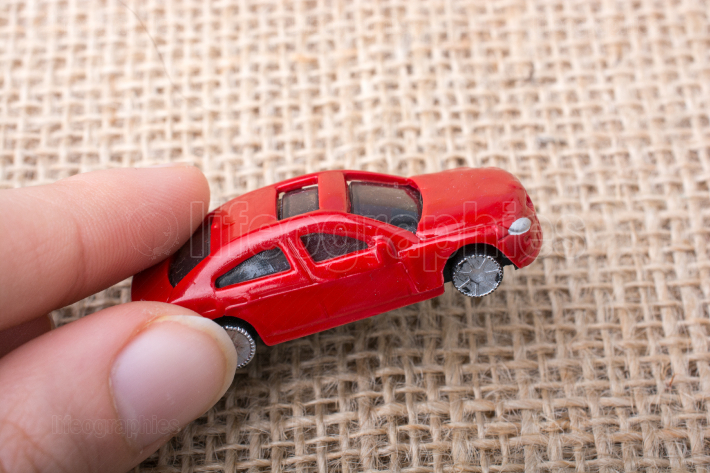 Colorful little toy car in hand