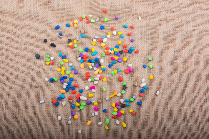 Colorful pebbles spread on canvas background