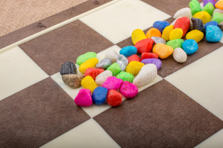 Colorful pebbles spread on checked board