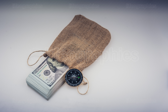Compass and bundle of US dollarin a sack