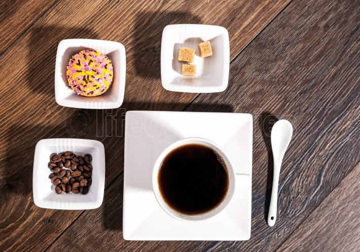 Cup of coffee with brown sugar, coffee beans and marshmallow bis