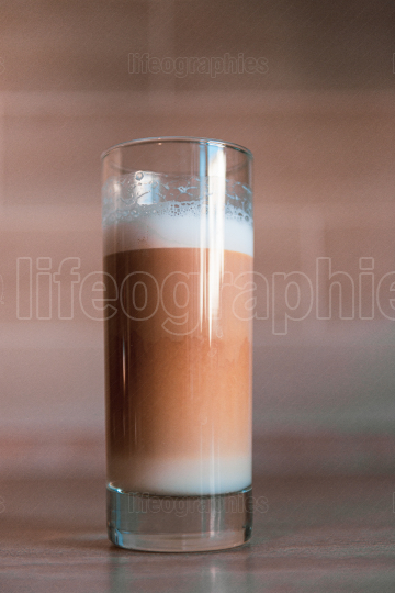Cup of multilayer coffee in a glass cup on brick background