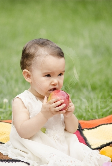 Cute little girl eating a red apple