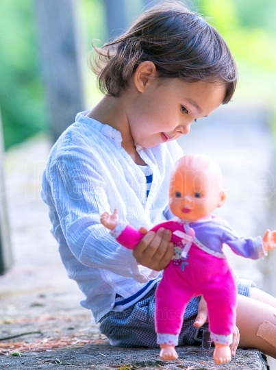 Cute little girl holding her doll