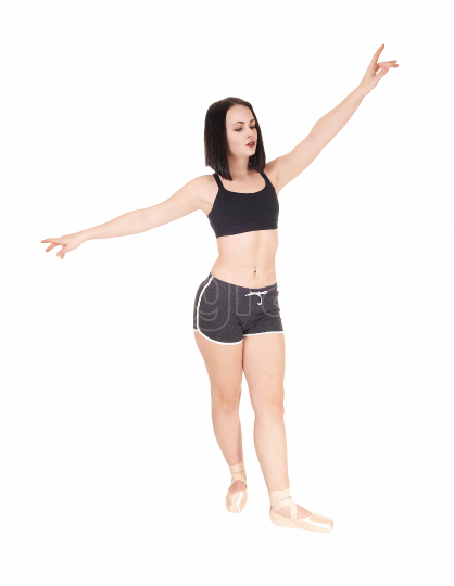 Dancing young woman standing hands raised in shorts