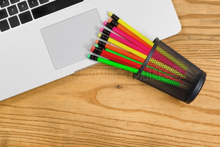 Desktop with colorful pencils on top of computer