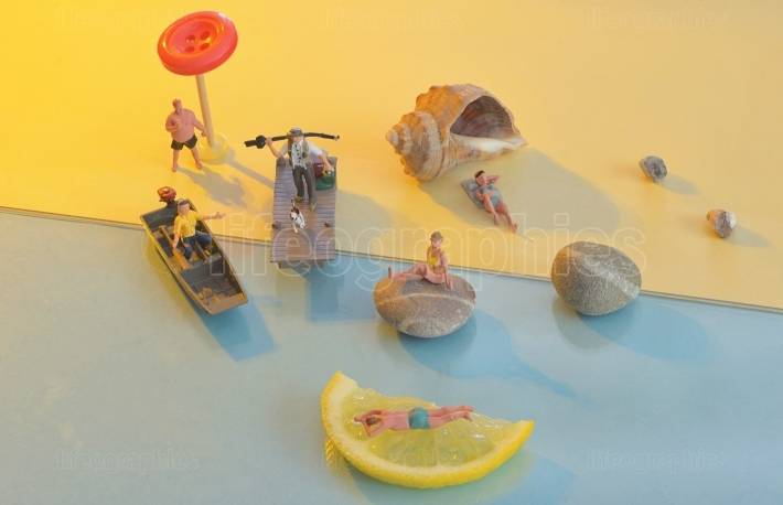 Different miniature people on the beach