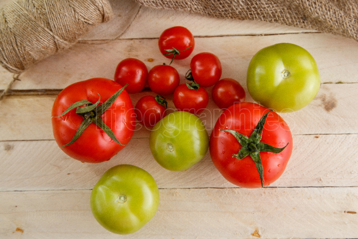 Different types of tomatoes on a light wooden background