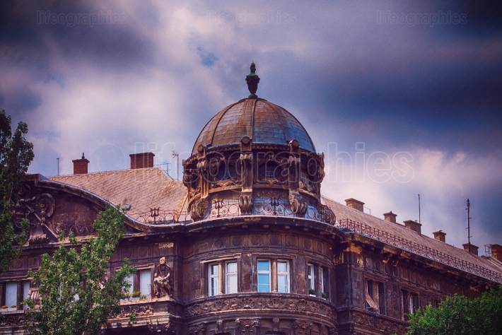 Domed old building with dark blue stormy clouds