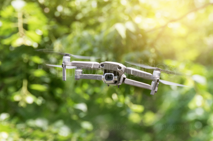 Drone quadcopter in flight on green blurred background