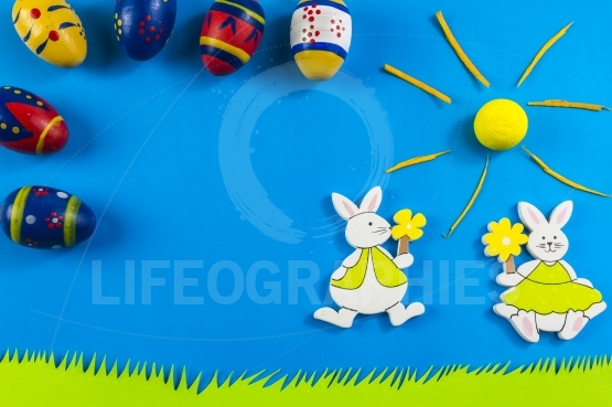 Easter bunnies and colored eggs on blue background