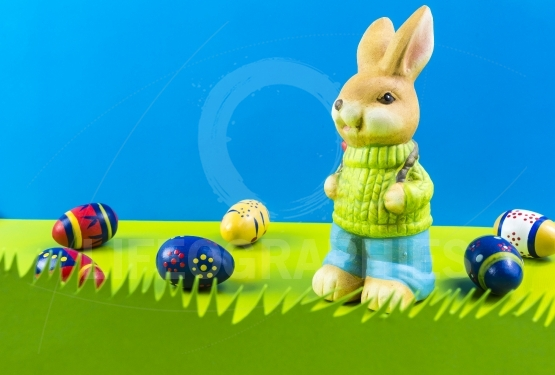 Easter bunny playing on grass on blue background
