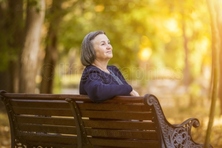 Elderly woman sitting on a bench in autumn park