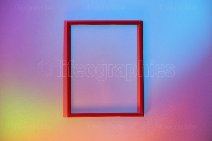 Empty Frame Hanging On A Colorful Wall