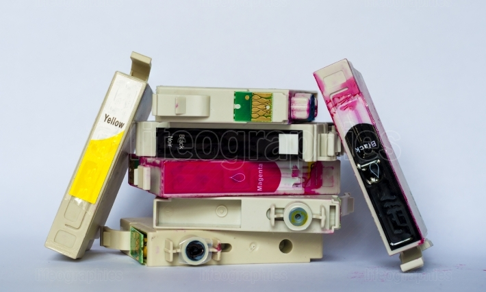 Empty ink cartridges with labels of various colors stacked on white background