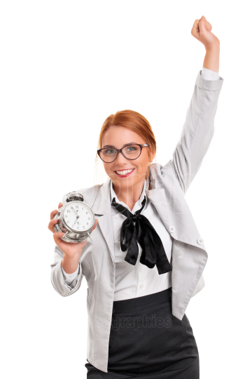 Excited young businesswoman with alarm clock celebrating