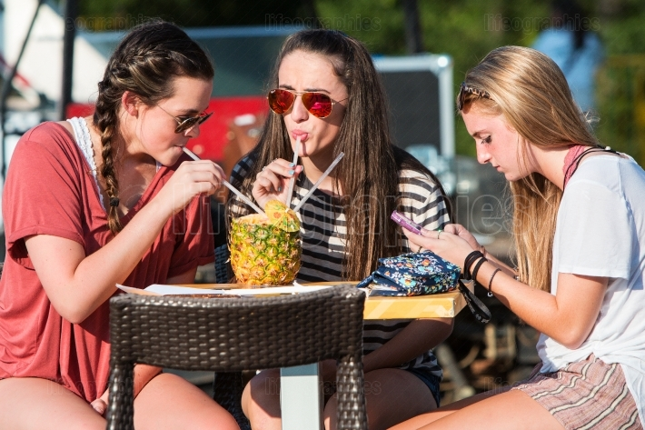 Female College Students Sip Fruity Drink From Pineapple At Festi