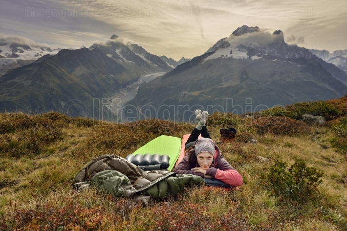 Female hiker relaxing near a large valley.