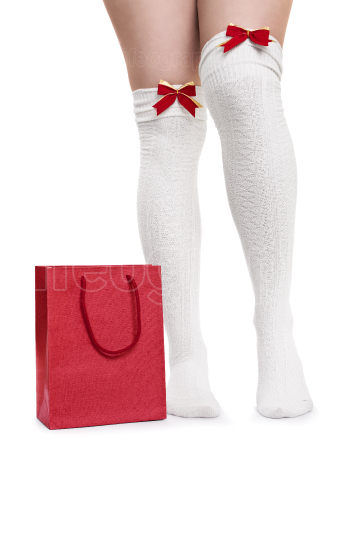 Female legs in white stockings next to a gift bag