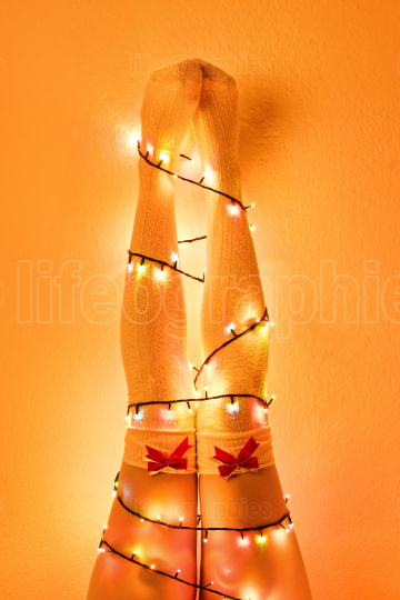 Female legs wrapped with christmas tree lights