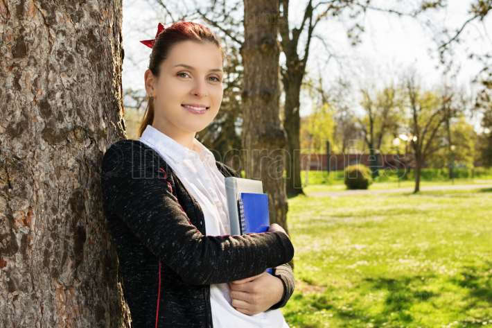 Female student leaning against a tree holding books