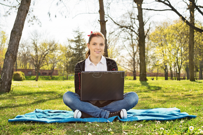 Female student sitting in a park with her laptop