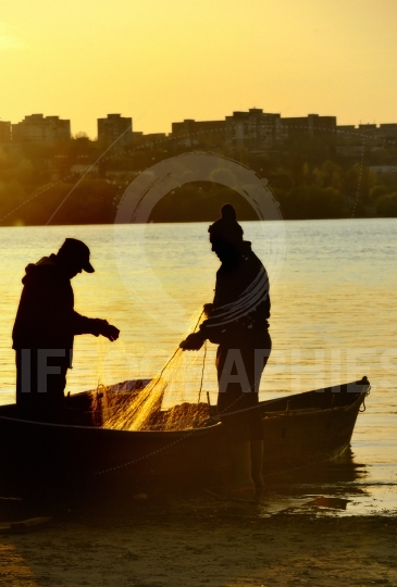 Fishermen silhouette at sunset
