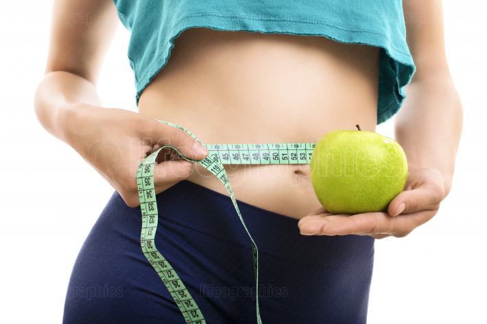 Fit girl measuring her waist and holding green apple
