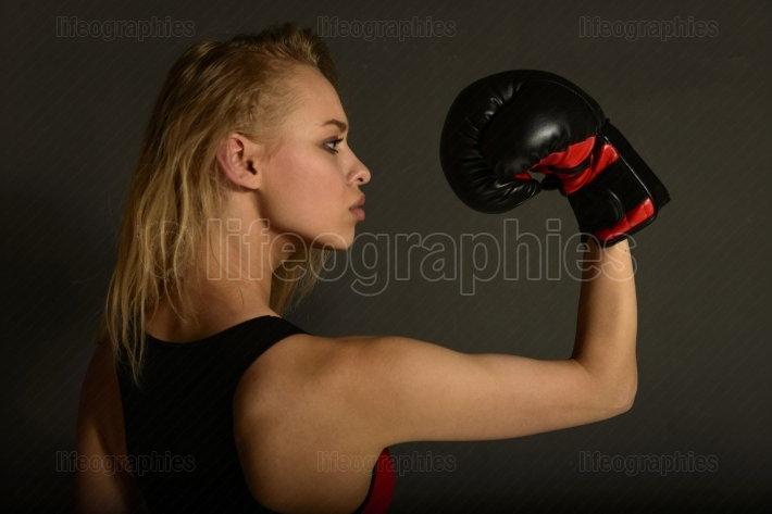 Fit slim young beautiful blonde woman boxing in sportswear