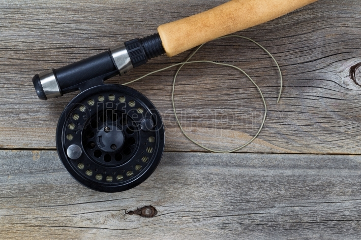 Fly Fishing Reel and Line on rustic wood